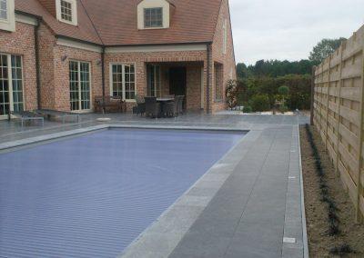 Zwembad met natuurstenen rand en solarrolluik als afdekking.